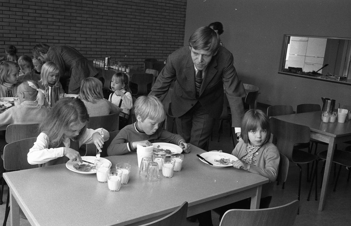Skolchef Per Thorstensson visar skolan för blivande elever. Barnen kommer från lekskolan. Ett besök i skolbespisningen ingår. Barnen sitter vid flera bord och äter. De har mjölk i glasen.