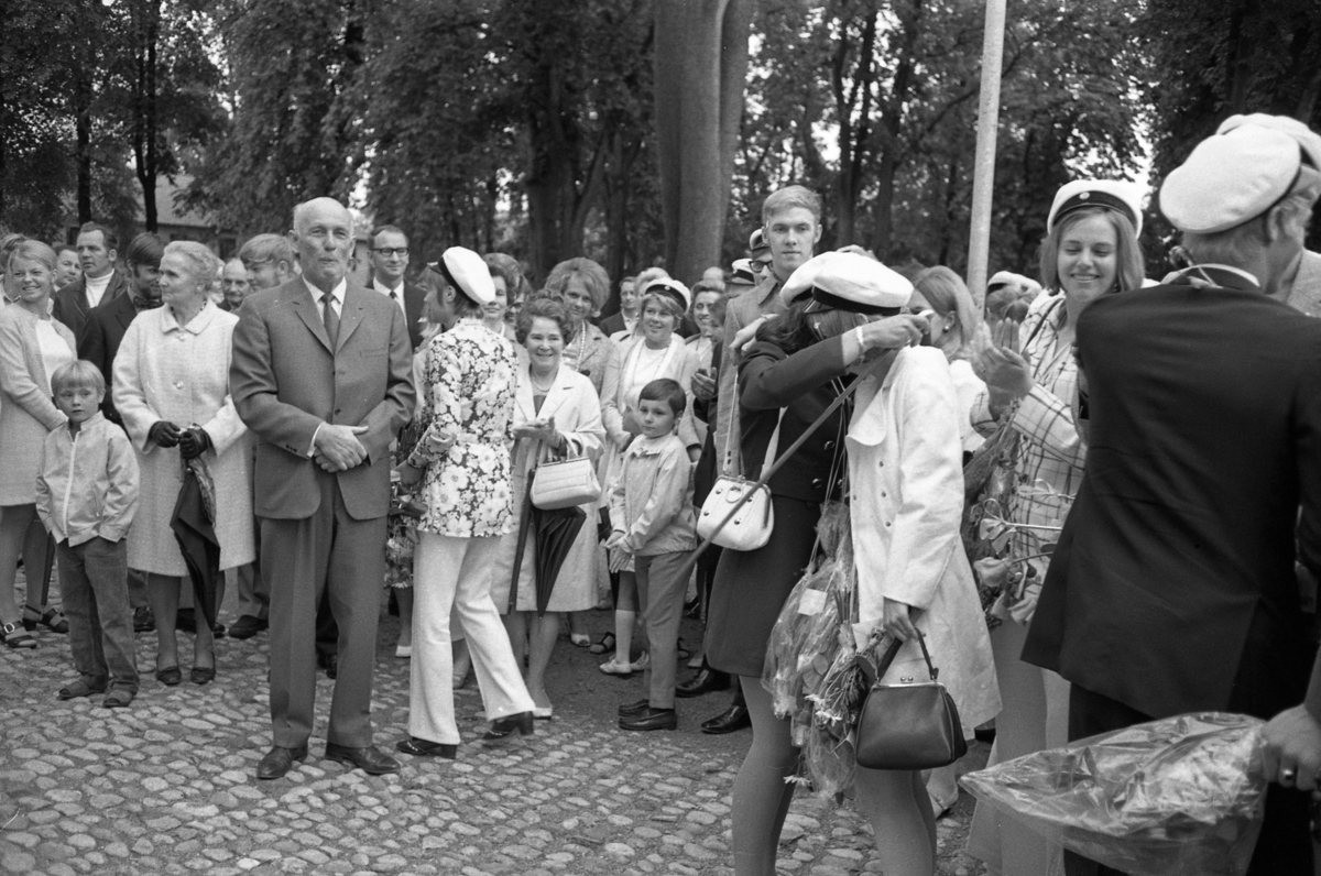 Studentdag! Den äldre mannen i kostym är rektor Bror Gustavsson. Till höger om honom, står Berta Holm, med paraply och vit handväska. Hon tittar på sin dotter, Kicki Holm, som blir omfamnad av studentkamraten Susanne Levert. Bakom Berta syns Mases Carita Danielsson.