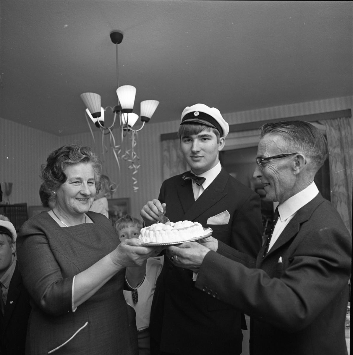 Lars-Göran Rådström har klarat studentexamen. (Han tillhör den sista kullen med muntliga förhör). Mamma Karin och pappa Egon håller i tårtan.