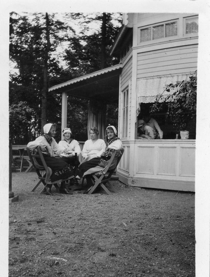 Stureparken, fyra kvinnor sitter i trädgårdsmöbler utanför ett hus. Tre av kvinnorna ser ut att bära folkdräkt. I fönstret syns en pojke med keps. Är det servering i huset?