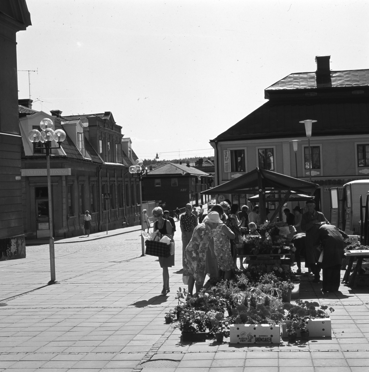 Torghandel. Nanny och Göte Lundin sköter blomsterförsäljningen. Intresserade kunder flockas vid blommorna. Pelargoner står i pappkartonger och buketter i hinkar. Platsen är Stora Torget, framför Konditori Centrum. Till vänster ligger Rådhuset. Arboga Tidnings kontor, Kapellbron och kvarteret Garvaregården ses i bakgrunden.