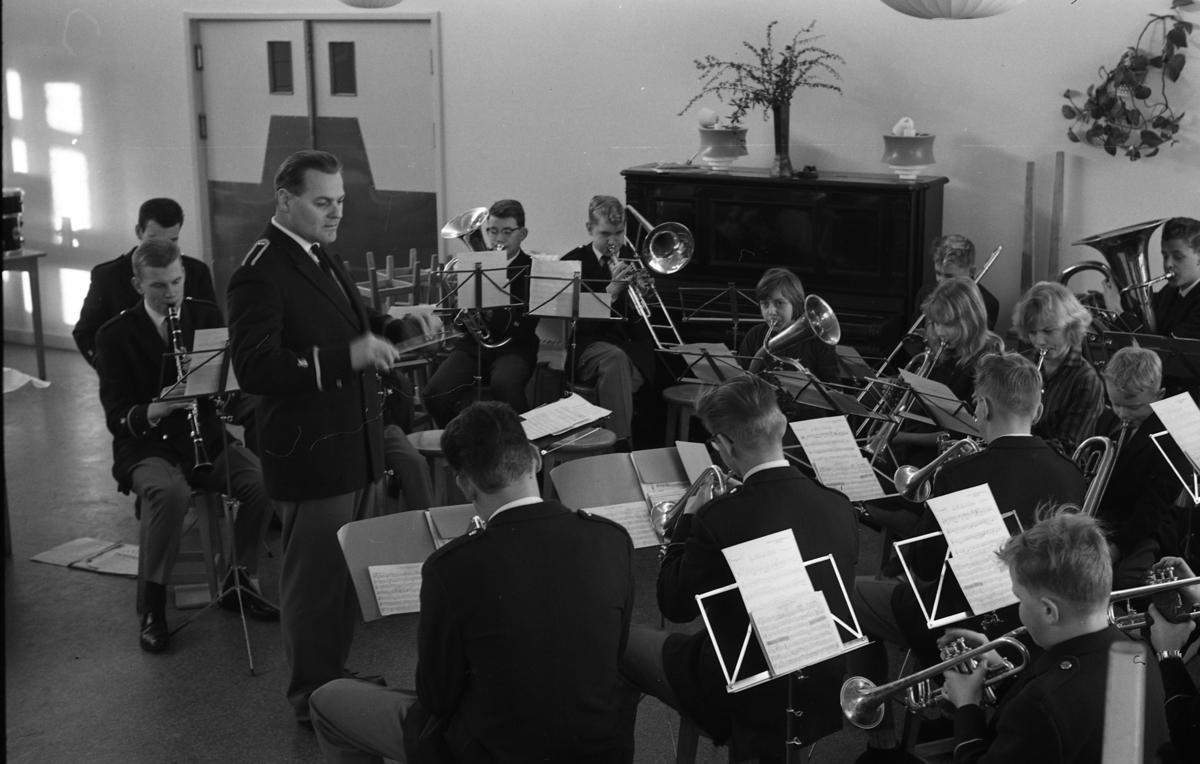 Ungdomsorkestern/Blåsorkestern uppträder. Dirigenten och de flesta av musikerna är klädda i uniform. Notställen är uppställda. I bakgrunden står ett piano.