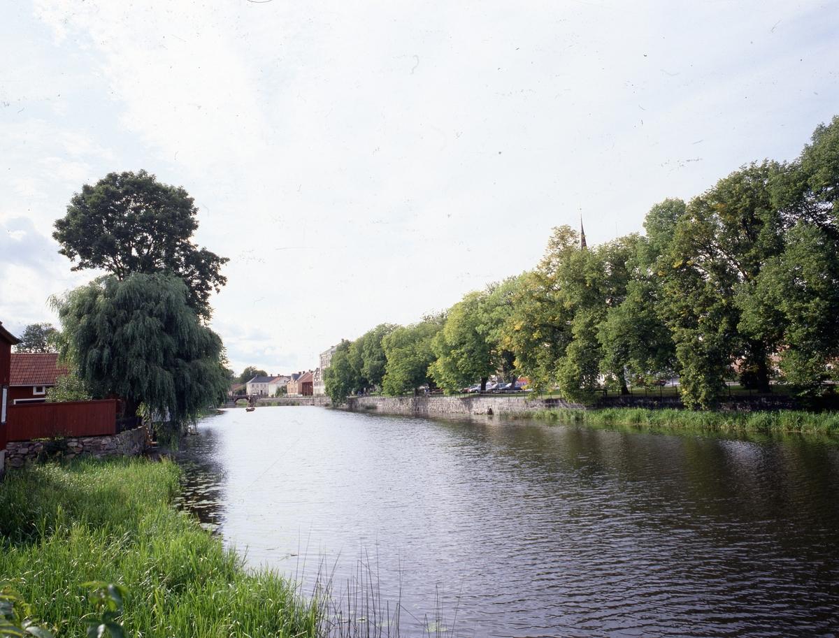 Vy mot Kapellbron och gångstråket vid Strandvägen. Tornet på Heliga Trefaldighetskyrkan syns över träden. En båt ligger i Arbogaån.