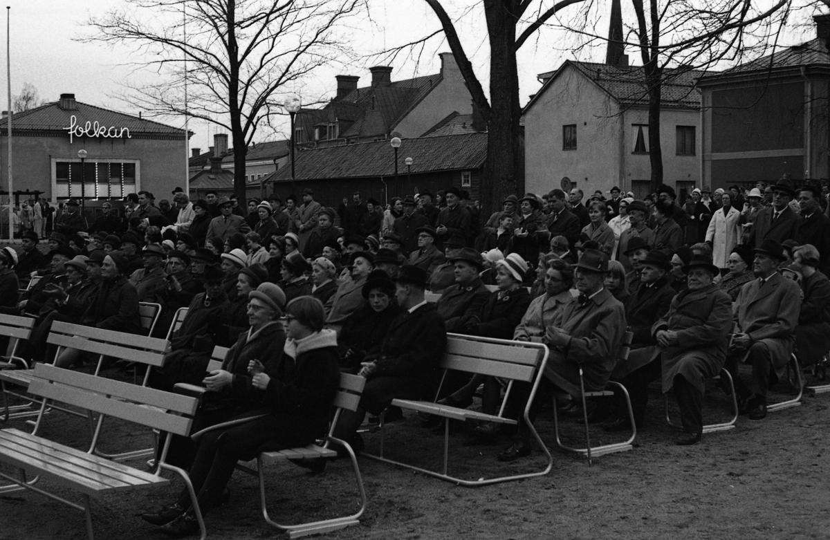 Vårens ankomst firas i Olof Ahllöfs park. En stor publik är samlad. De sitter på bänkar eller står runt området. Till vänster ses Folkan, Medborgarhuset, och husen på Ahllöfsgatan. Sista april, Valborgsmässoafton.