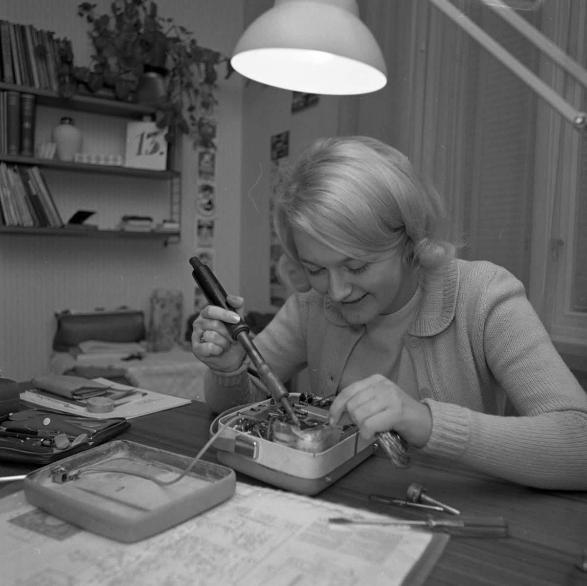 Ann-Britt Gustafsson, årets Lucia. Ung kvinna som sitter vid skrivbordet. Framför henne ligger en isärtagen teknisk apparat. Hon håller en skruvmejsel i ena handen. Fler mejslar liggar på skrivbordet. En skrivbordslampa syns. På väggen hänger en bokhylla, modell String, med böcker, prydnadssaker och en krukväxt.