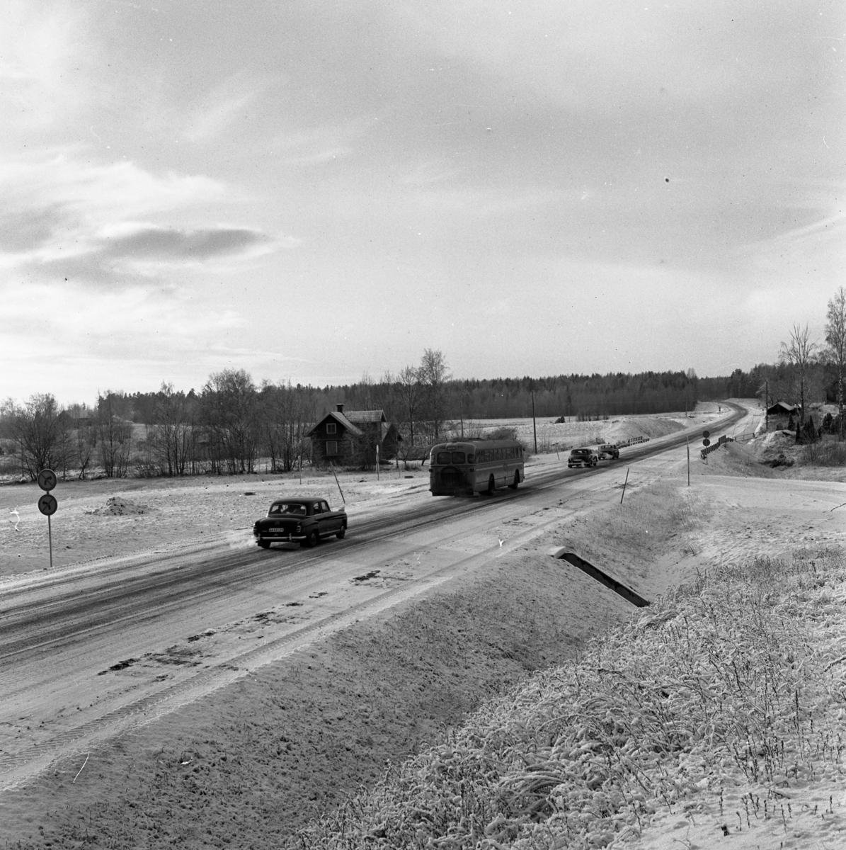Örebrovägen öppnas efter ombyggnad. Personbilar och buss. Det är vinter och snö.
