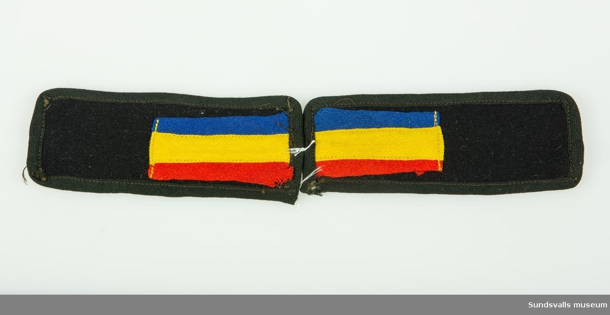 Axelklaffar av svart ylle med ett rött-, gult- och blårandigt band i ena änden på båda klaffarna.