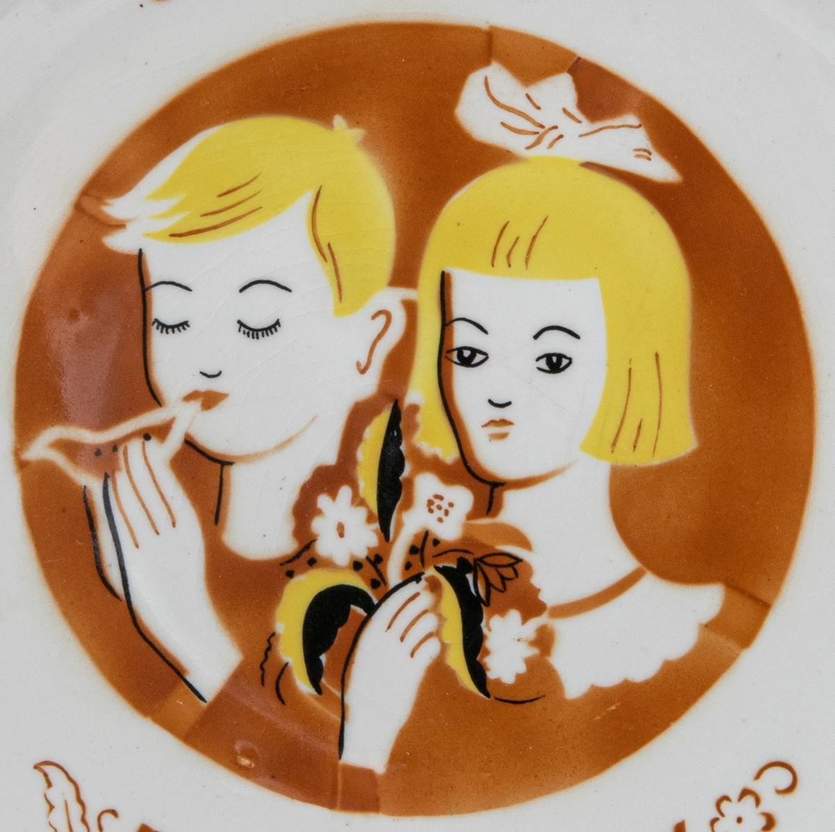 """Minnestallrik, i gulvit glasyr med brun, gul och svart dekor föreställande en pojke som spelar på en lergök och en flicka med rosett i håret som håller en bukett blommor. På tallriken texten """"8-12 sept.1943 Barnens dag."""""""