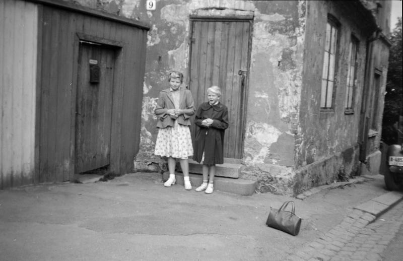 Bildet er fra Johannesgata. Jeg Wenche Olsen bodde med mamma og pappa der, fram til ca. april-mai 1945. Jeg var ca. 2 år. Det var kun et rom med strøm, men ikke innlagt vann. Bildet er tatt før Bodil Rødberg Larsen og jeg skulle reise på feriekolonien. Vi skulle være på forskjellige steder. Koloniene var på Hadeland. Veska som står i forgrunn er min. Tror Bodil er 8-9 år og jeg 9-10 år. Vi var pene i tøyet fordi det var reisetøy, som ble hengt bort under oppholdet. (Foto/Photo)