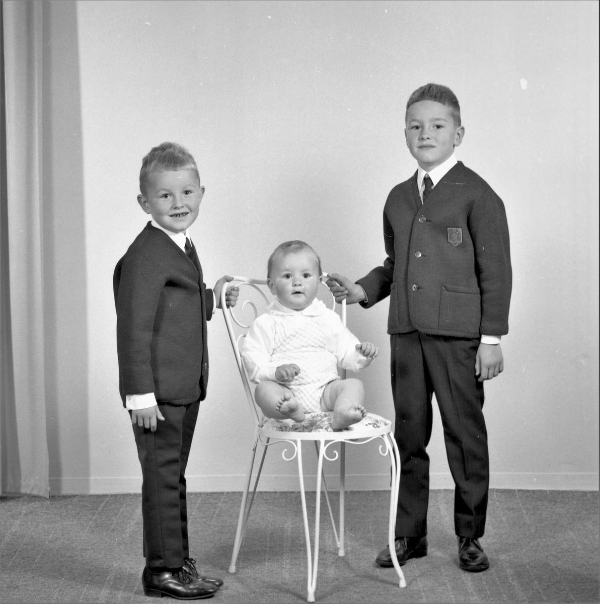 Portrett. Gruppe på tre. Liten lyshåret gutt i lys skjorte