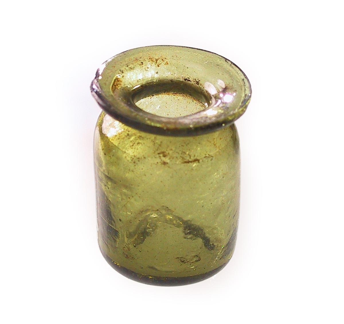 Lite glass, enten medisinglass, blekkhus ell. lign.   Gulgrønt, blåst glass, sylindrisk, med innsnevring og krave  på toppen.