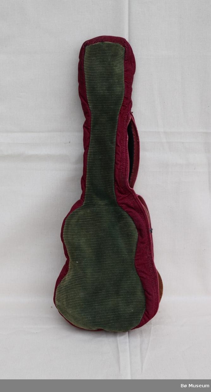 Ukulele, med trekk, eid av Heidi Løvlund. Ukulela er av tre, brunlakkert og har kvit plast på stemmeskruane. Ukulela har mykje riper og skraper. Trekket er av grøn og bringebærlilla fløyel. Trekket er fora og har glidelås. Glidelåsen er ikkje lenger funksjonell.