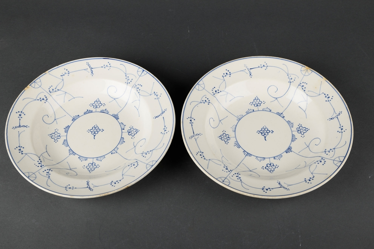 2 hvite skåler med blå håndmalt dekorasjon av bl.a. blomster.