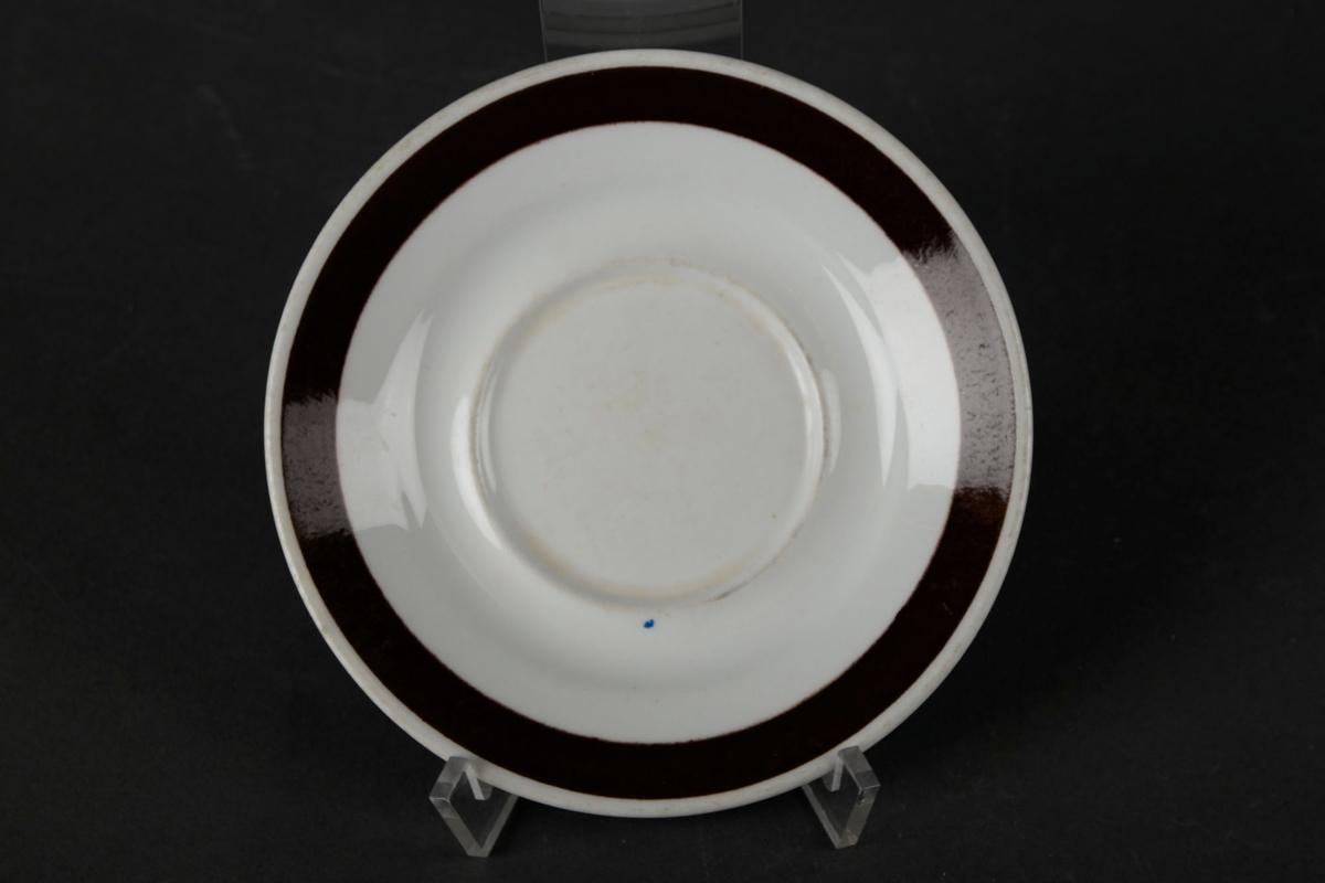 Hvitt tefat med en brun sirkel langs kanten.