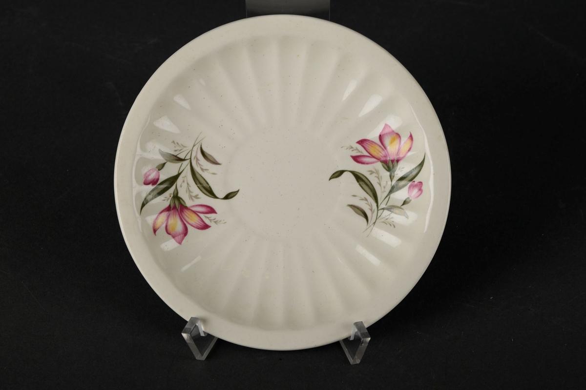 Hvitt tefat dekorert med to blomster på hver side av midten, og bølgete kanter på innsiden.