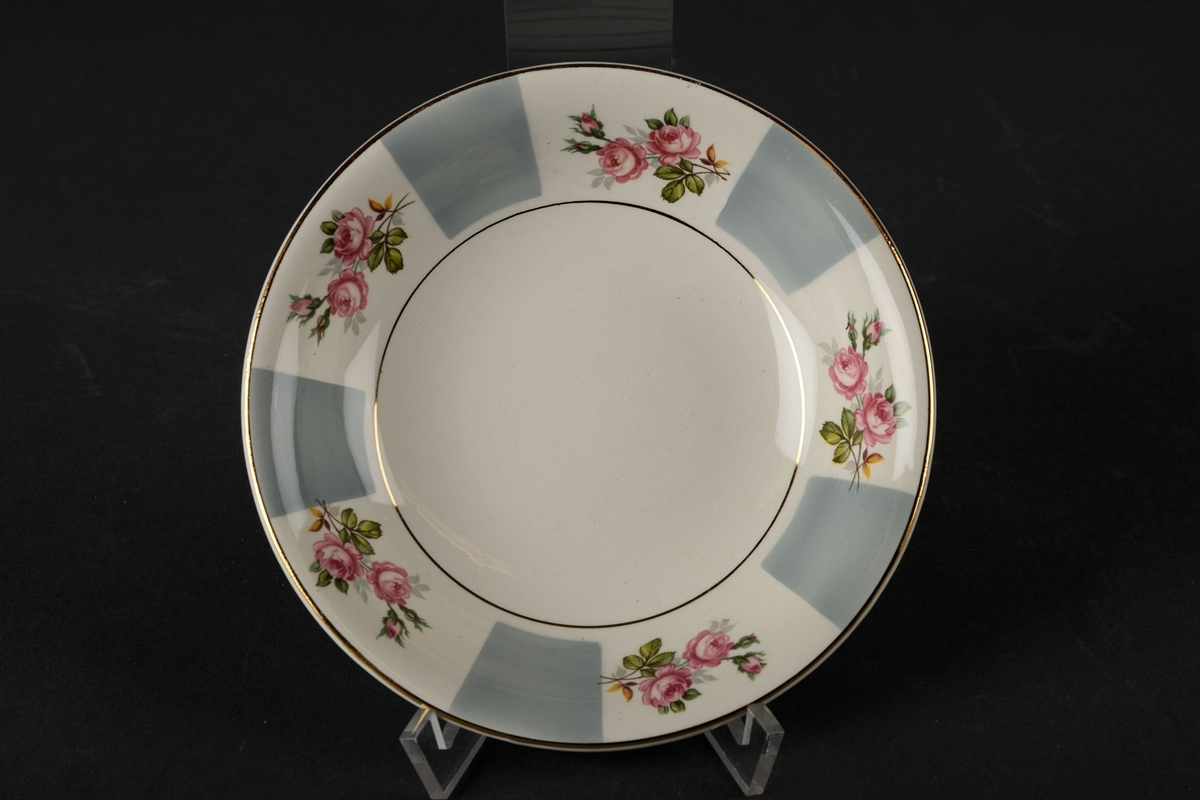 Hvit skål dekorert med fem grå firkanter og fem blomster langs kanten, og to gull-sirkler: en rundt bunnen, og en på kanten.