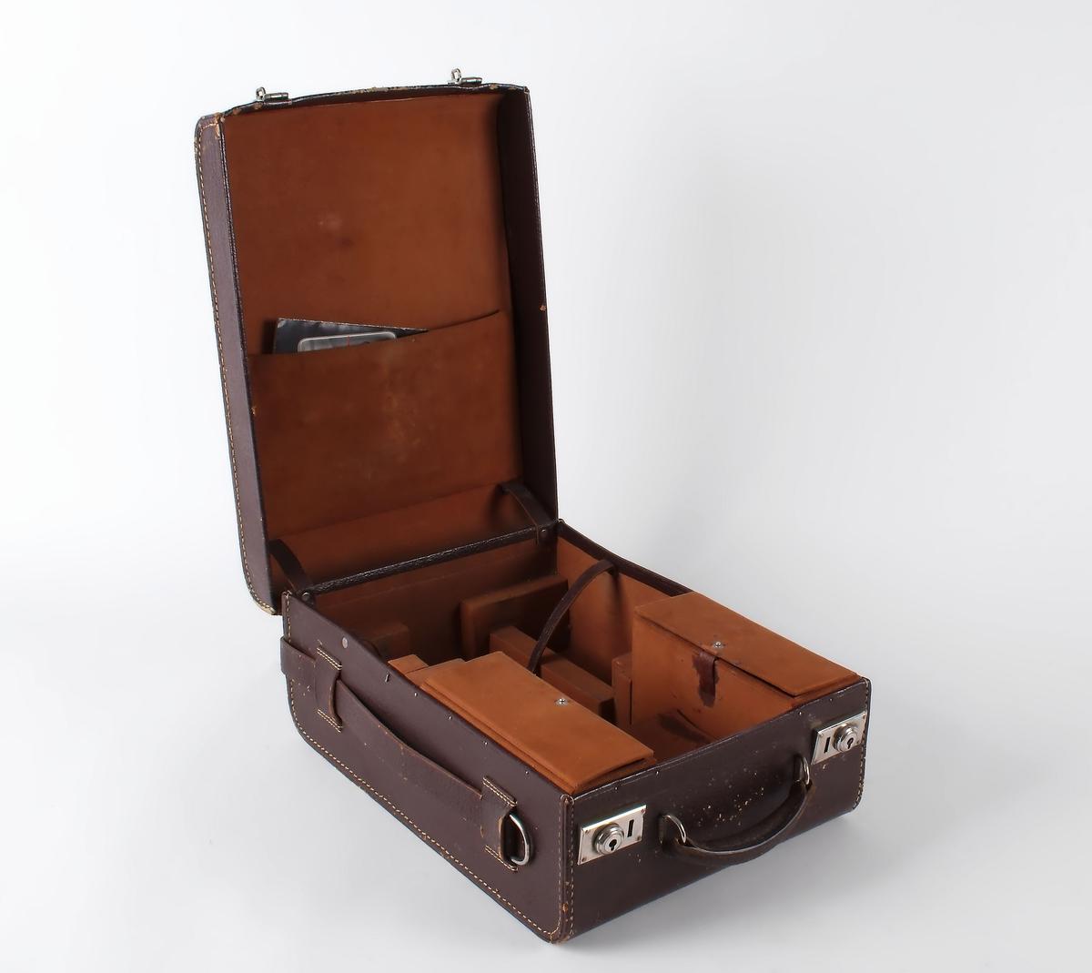 Sort filmkamera i brun skinnkoffert.