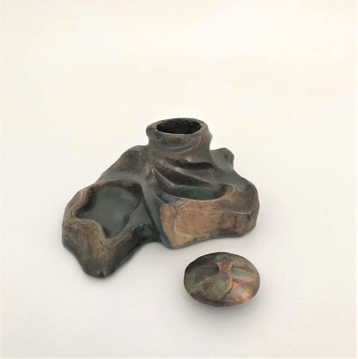 Blekkhus av steingods. Den asymmetriske formen minner om en klippeformasjon med avsatser i ulik høyde. Arbeidet preges av et organisk formspråk med slyngende linjeføringer. Blekkhuset er plassert på toppen og har et sirkulært lokk. Glasuren er holdt i brunlige fargetoner, mens blekkhusets fordypninger er grønnfarget.