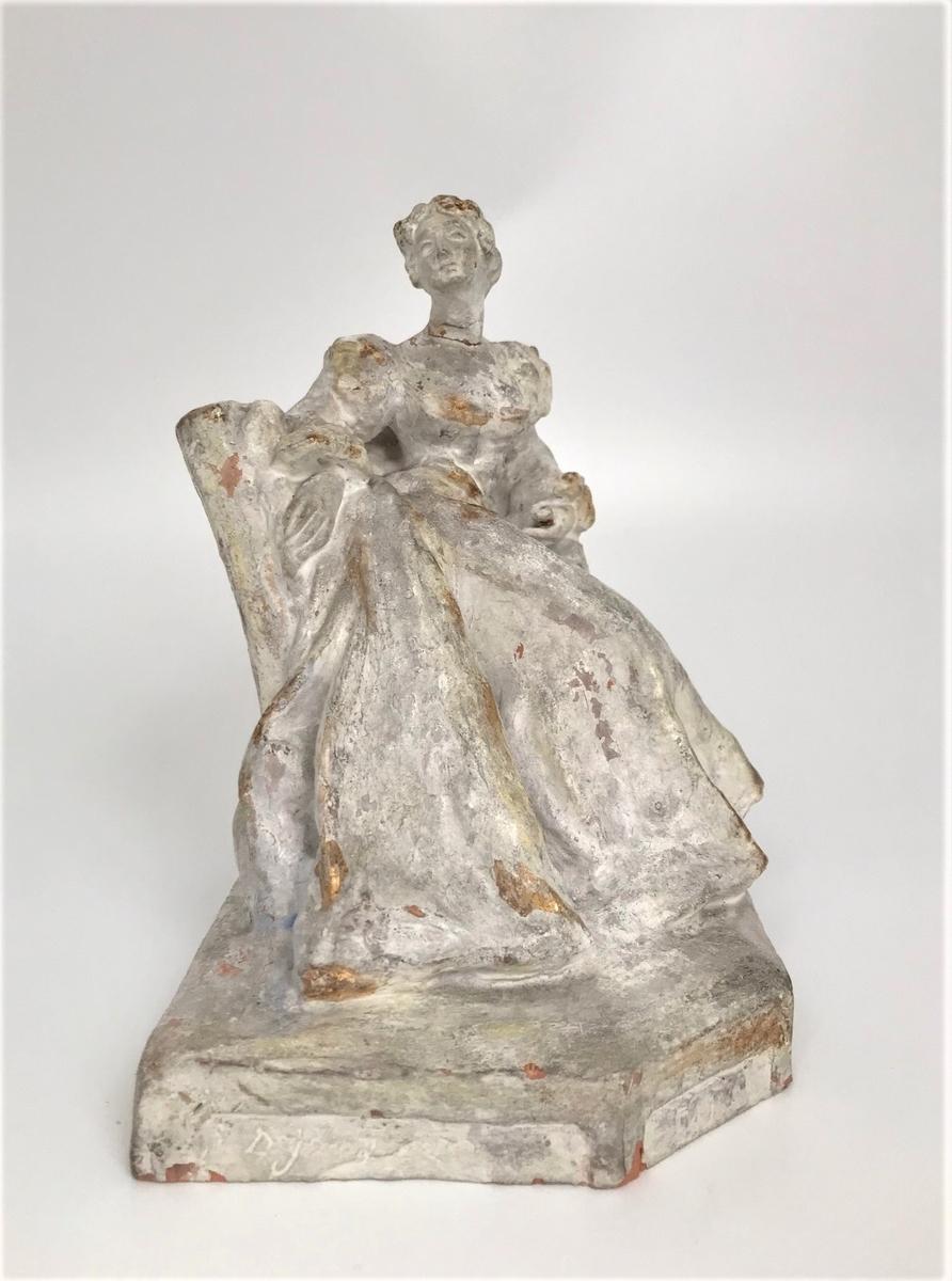 Terrakottastatuett med tilhørende marmorsokkel. Statuetten fremstiller en kvinne sittende i en lenestol, som vrir overkroppen svakt mot høyre. Hun har oppsatt hår og er iført en fotsid kjole. Terrakottaen bemalt med hvitfarge med innslag av forgylte og gul-grønne partier.
