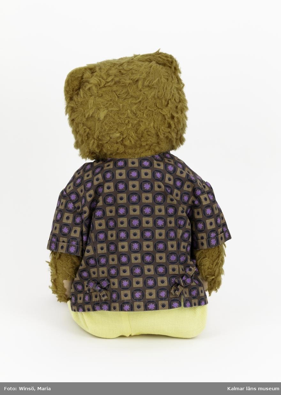 KLM 45519:12:1-3 Nalle med kläder, :1 nalle med brun päls och rosa tramdynor. Pärlögon och nos av garn. Har tidigare kunnat brumma men det fungerar inte längre. :2 blus, brun med rutmönster i lila och brunt. :3 byxor ljusgul våffelväv.