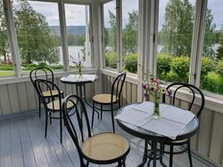 En glassveranda med to bord med blomster og stoler plassert rundt bordene.