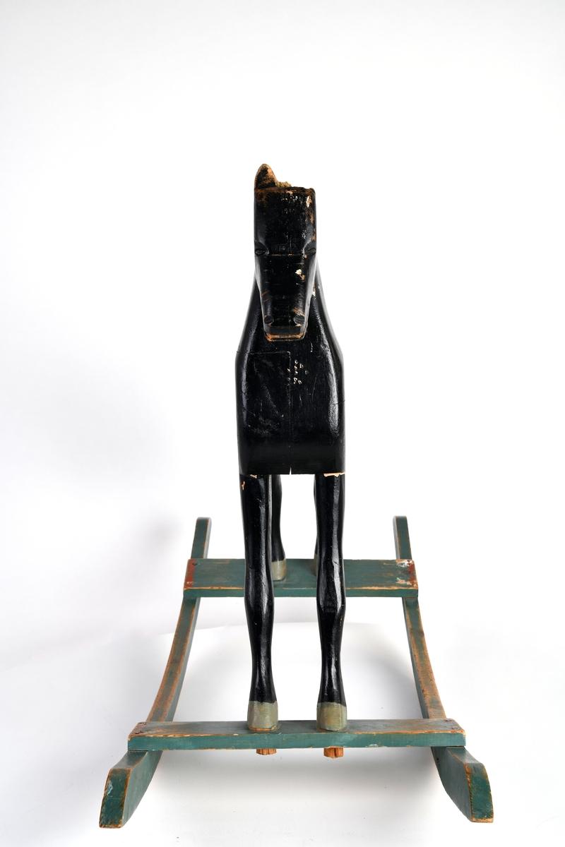 En gyngehest laget av tre. Hesten er skåret ut av flere deler og satt sammen. Øyne, mule og munn er skjært ut. Ørene har også vært skåret ut, men den mangler delvis/helt begge ørene. I nakken og på rompen er det rester etter naturfiber som har vært henholdsvis man og hale. Hesten er svartmalt, mens hovene er malt i en gråfarge. Sadel/dekken er malt i brungrått og rødt. Hesten står på grønnmalte meier. Meiene er buet. Foran og bak er det en tverrplanke. Disse er spikret på meiene. Hesten er festet til meiene ved hjelp av dissse tverrplankene. En treplugg fra hver hestefot er festet i tverrplanken.