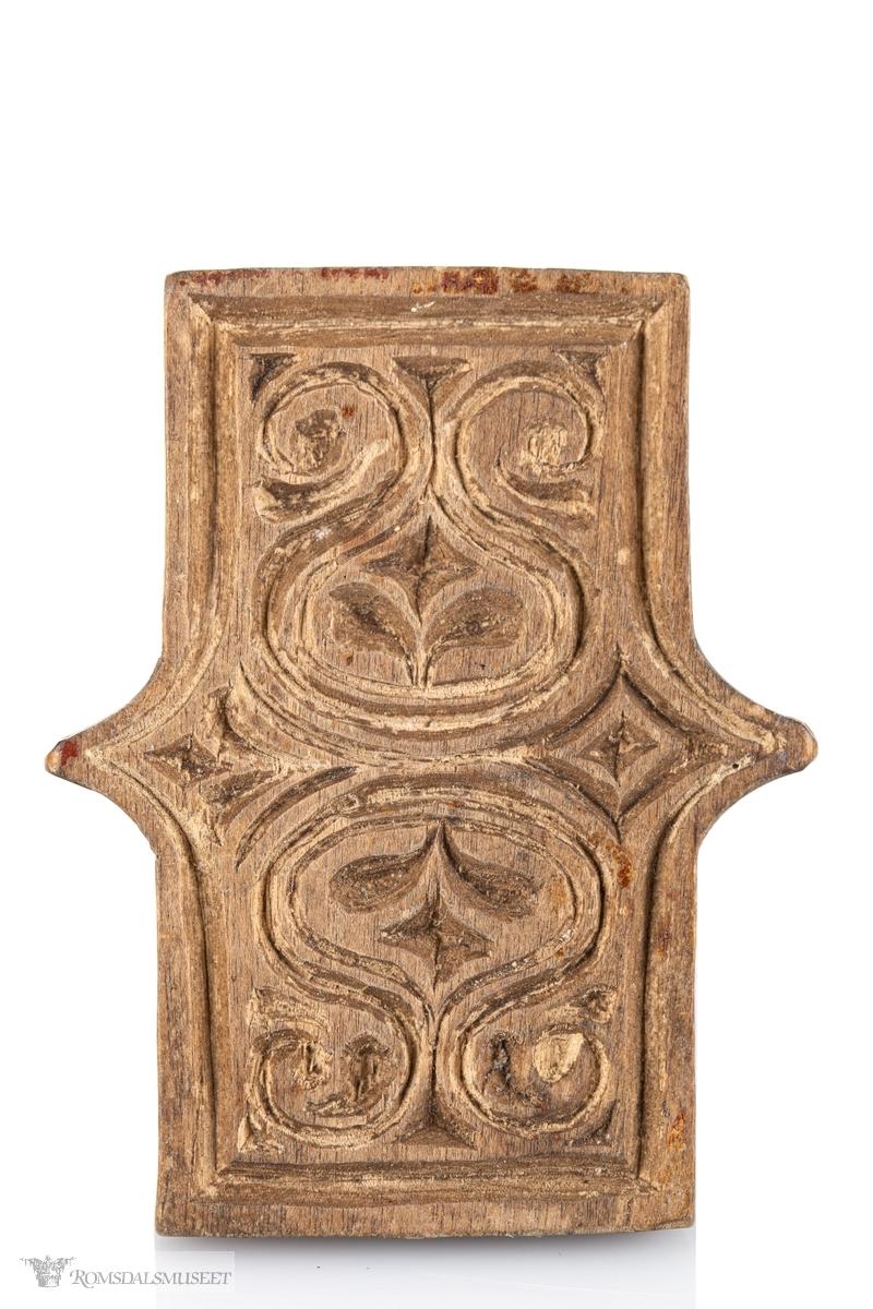Stemplet har fint og rikt symetrisk mønster med oval, buer og ruter. Grepet har også mønster på oppsiden, svart enkelt.