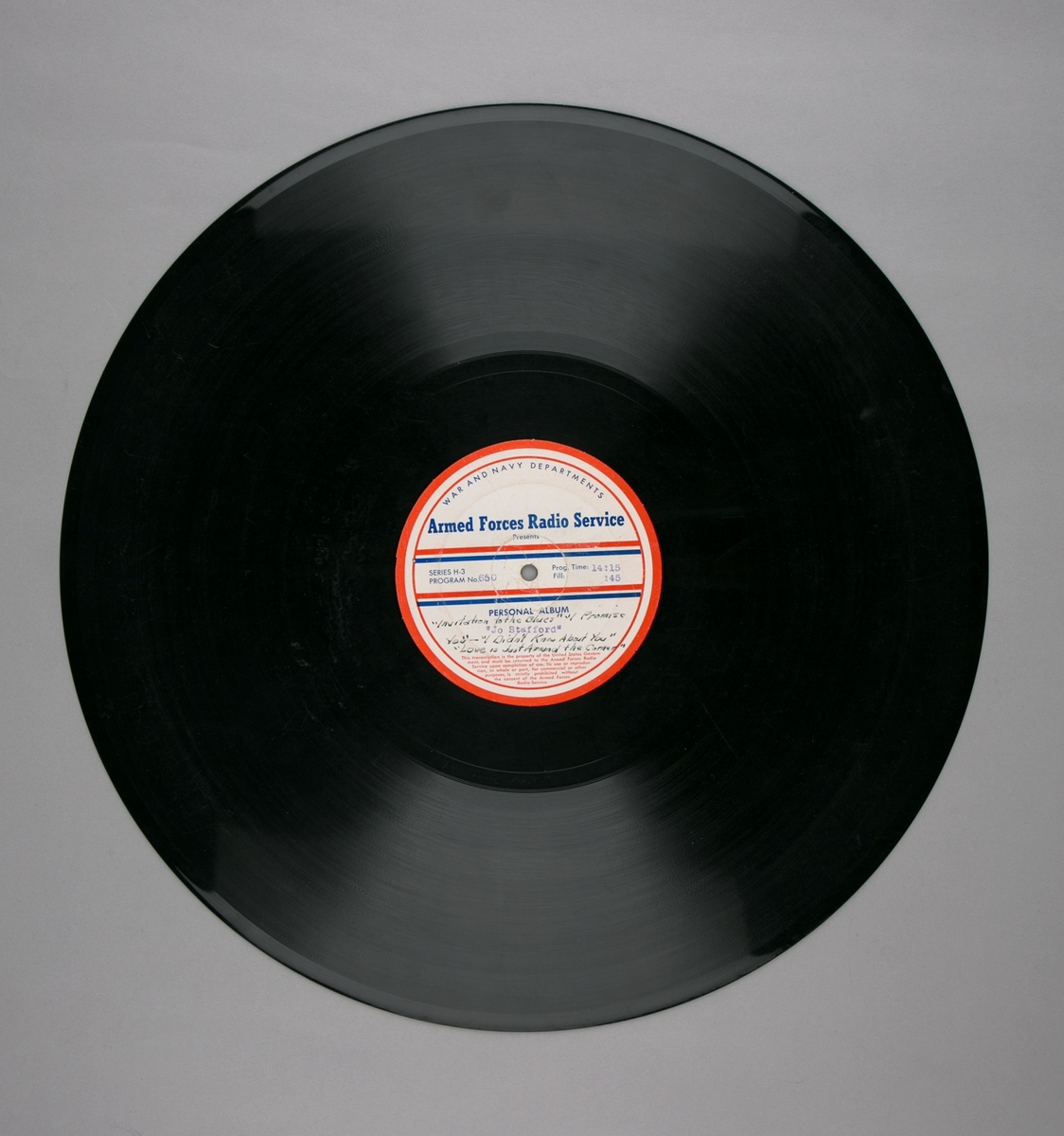 """Grammofonplatesamling. LP-plate med tittel """"Armed Forces Radio Service"""" utgitt av War and Navy Departements. Plate i svart vinyl spilles på platespiller med 33 1/3 omdreininger i minuttet (33-plate). I papiromslag."""