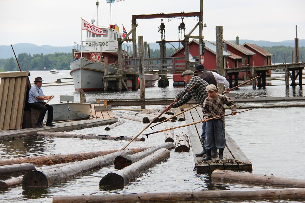 Fire tømmerfløtere med hver sin tømmerhake som fløter tømmer i elva og brygga på Fetsund lenser