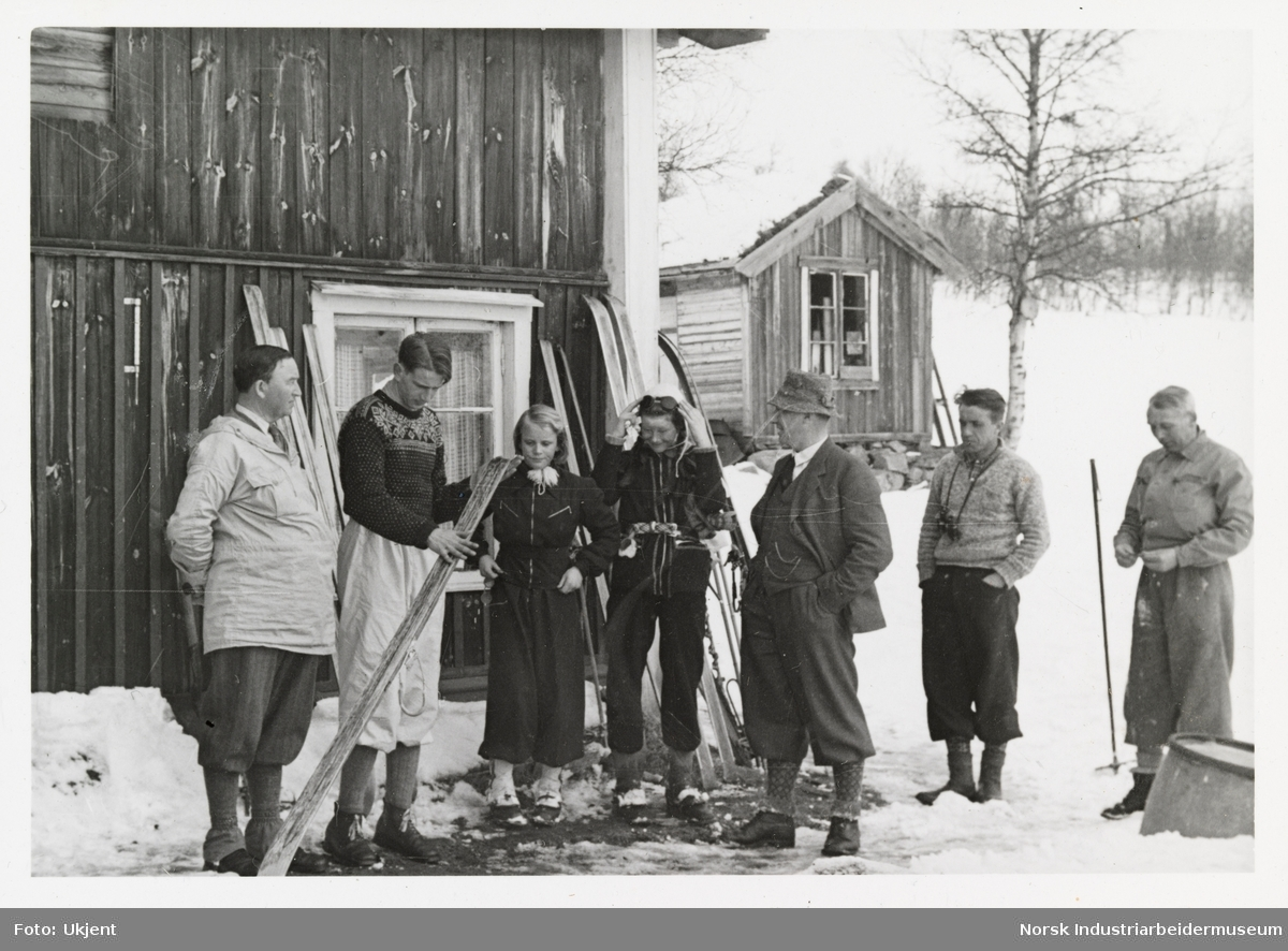 Mennesker i turklær står utendørs foran hus.  Ski er plassert langs husveggen
