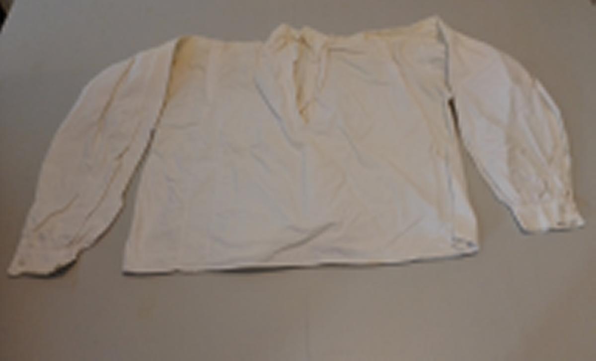 Rettklypt bol skøytt med smal innfelling på breidda. Legg på skuldrene. Splitt framme under ståkrage. 5 smale vertikale legg under kragen i ryggen. Langt erme foldelagd til skulder og rykt til knappa ermelinning. Innfelt små kilar i ermehola
