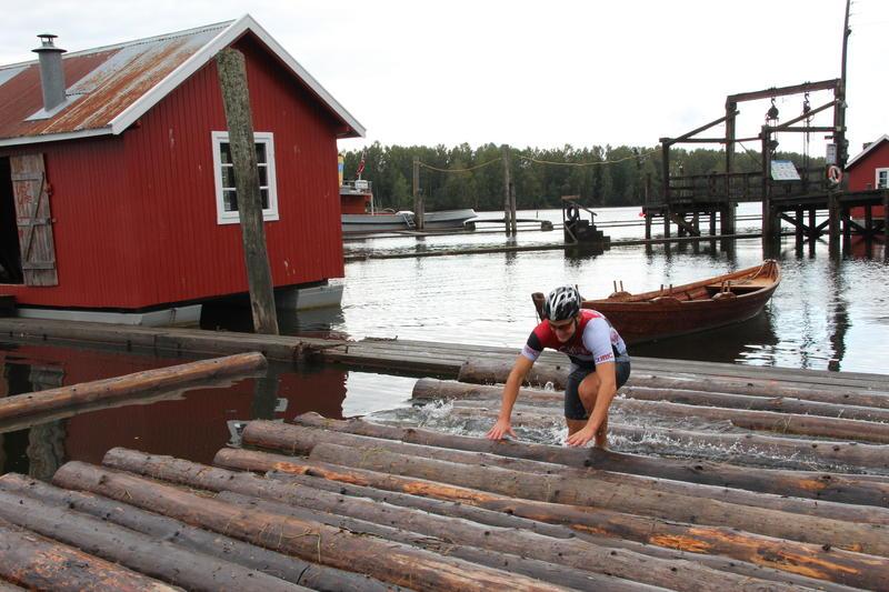 Mann som løper på tømmer i elva med sykkeltøy og sykkelhjelm. I bakgrunnen hvilebrakke og robåt