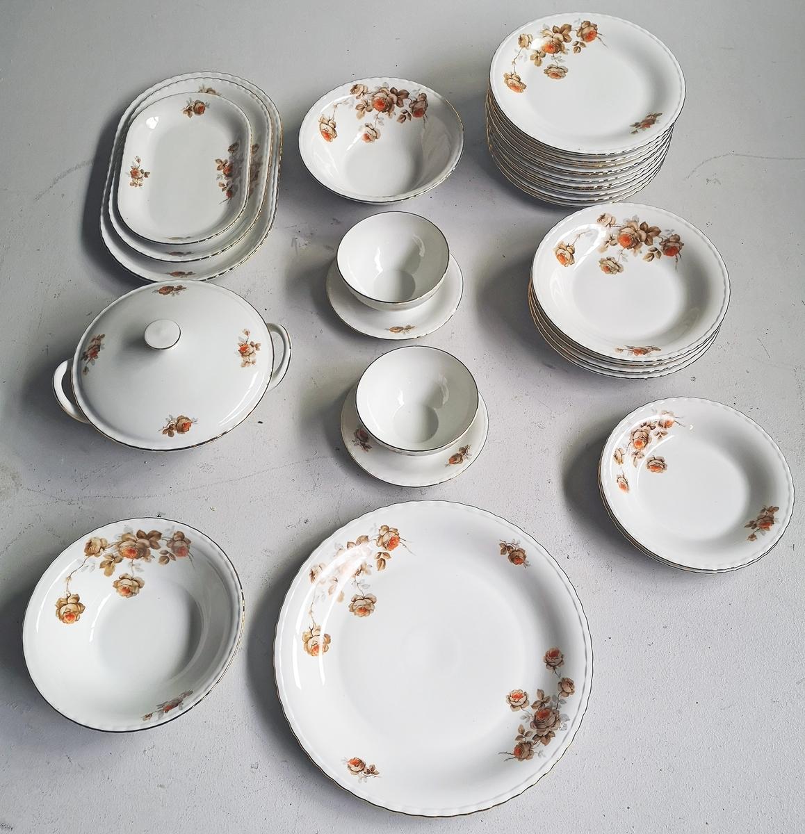 Middassservise - 12 middags tallerkenar - 12 suppe tallerkenar - 12 dessert skåler - 4 serveringsfat - 2 serevering skåler/ei med lok - 2 sause skåler - 1 saft/dessertsaus mugge  Bølgeforma kant med gull rand - Stilisert rose dekor.