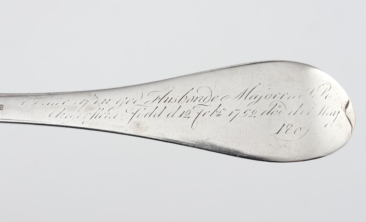 "Sked av silver. Svensk trubbig modell. På skaftets baksida inskription: ""Minne af en god husbonde Majoren I.R. Angerstein, Född d. 12 febr. 1752, död d. 11 maj 1809""."