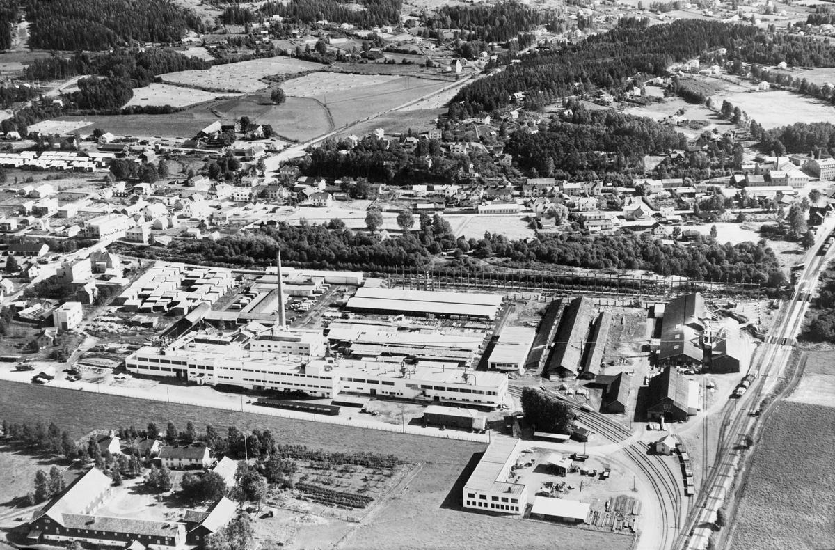 """Flyfotografi (svart-hvit papirkopi) av fabrikkanleggene til hjørnesteinsbedriften Berger Langmoen i Brumununddal, Ringsaker kommune, Hedmark fylke. Sannsynligvis er bildet tatt i perioden 1952-1954.  Sagbruket i bildet er den """"gamle"""" saga, det vil si den første saga i dette området. (Berger Langmoens første sag brant ned i 1934. Den var plassert ved det som i dag heter Berger Langmoens veg, Holen området. Etter brannen ble bedriften gjenoppbygd på Granerudenga.) I forgrunnen av bildet ses ses sentralverkstedet. Parkettfabrikken som kom i 1962/63 er ennå ikke bygd."""