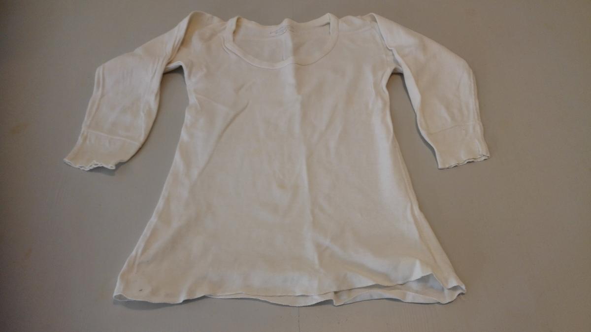 """Form: a)trøye:Rund halsringing.  Eit sett undertøy til born.  Langt erme med """"brot""""/ vrangbord kring handleddet. b)Underbukse med lange føter. Vrangbord kring ankel. Elastikk i løpegang rundt livet. Smettegylf i front."""