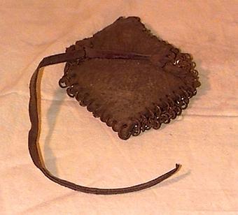 Fyrkantigt ylletyg som är beklätt med ett nät av cirkelformade metallringar på ena sidan, och har en läderrem på andra sidan.