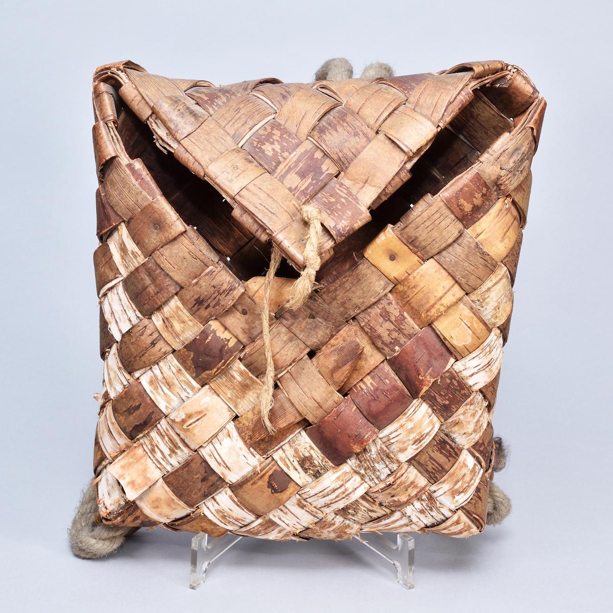 Kont flätad av näverremsor, stående rektangulär med triangulärt fällock. Tillslutes med sekundärt snöre och trätapp. Bärremmar i form av rep.
