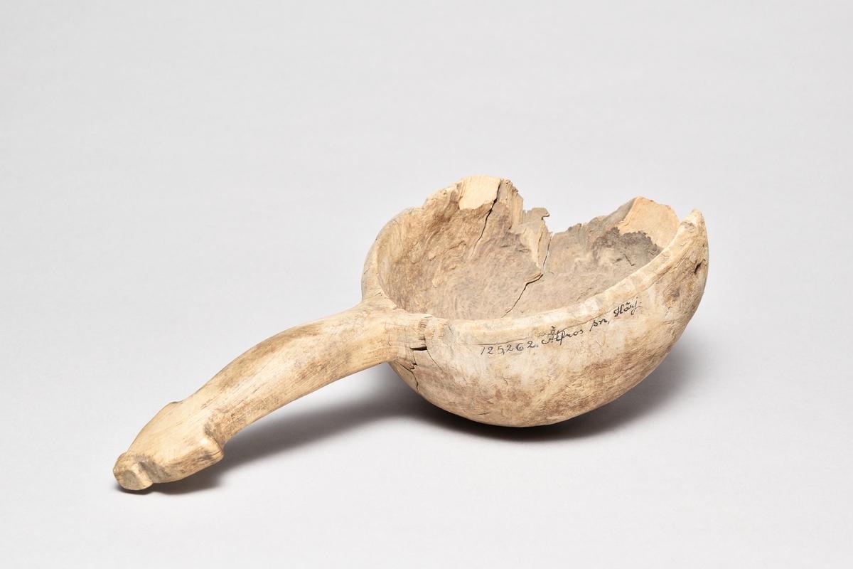Skopa av omålad masur, rund, profilerat skaft, lagad i botten med tenn. Stor del av skopans främre del saknas.