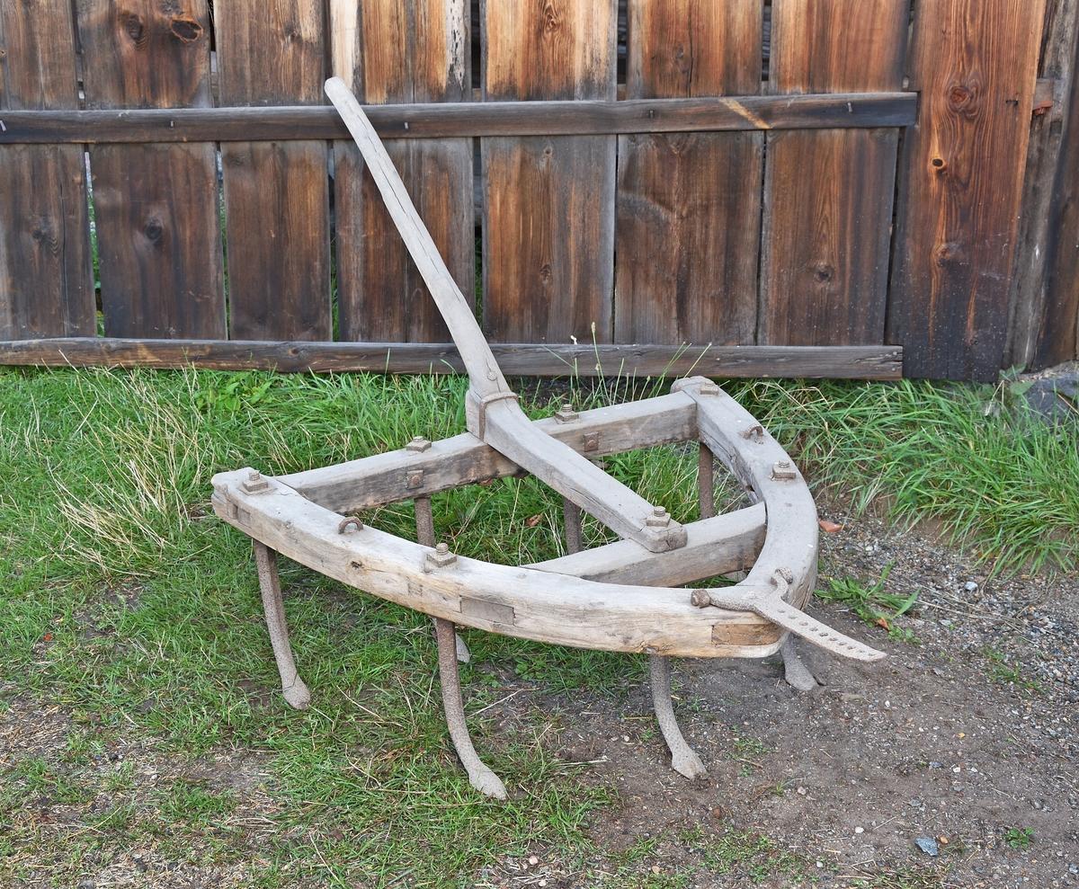 Klösharv av trä och järn. Tringelformad ram, gåsfötter av järn, tre fram och fyra bak. Handtag. (Skaklar saknas.)
