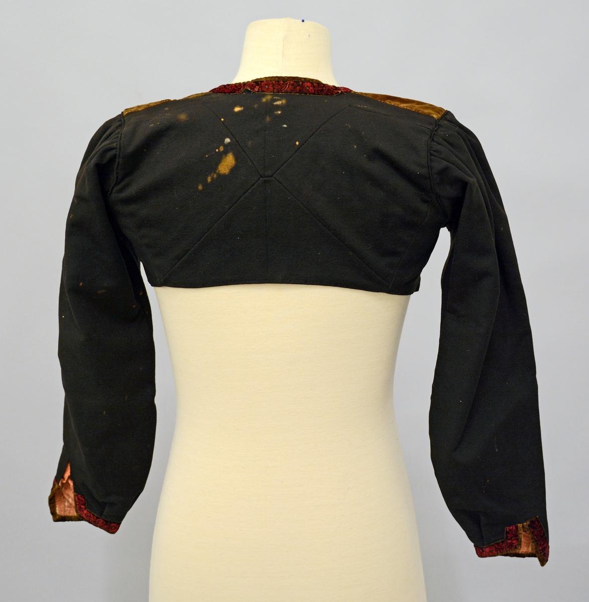 Kvinnetrøye i svart klede uten krage. Trøyen kan ikke lukkes: jakkeslagene går i en skrå ned til hver sidesøm. Baksiden er sydd sammen av 4 stk trekanter på midten. Ermene er rynket på baksiden. Dekoren er  kanting av brunt fløyel og et bredere mørkerødt bånd foran og på emsplittene. Samme brune tøy er benyttet på skuldrene. Innvendig er trøyen hel fòret med mønstret bomullstøy.Trøyen er misfarget bak og har små hull.