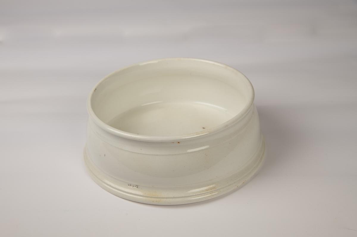 Rund spyttebakke med lav profilert stett, svakt  skrånende sider med en ring øverst og svakt utsvunget munningsrand.