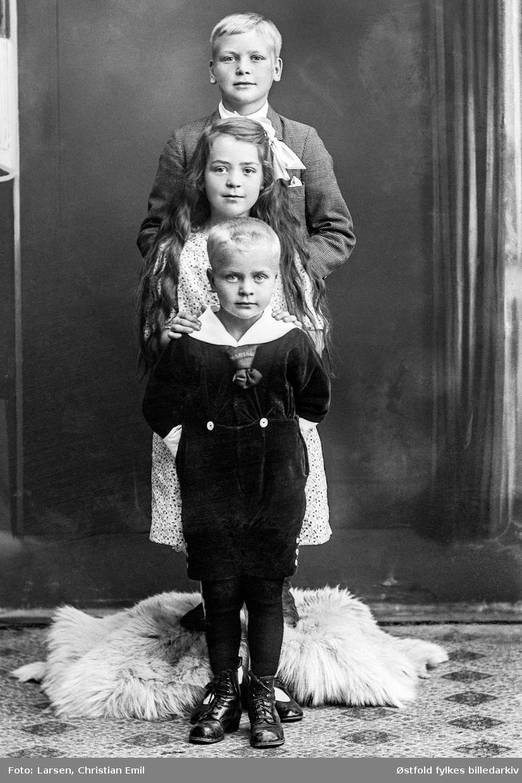 Gruppeportrett av barna til Laura (pikenavn Sørensen) og Christian Jensen Fladeby fra Åslien, Skjeberg 1919. Foran: Reidar Fladeby foran, Bakerst: Jens Fladeby og deres søster i midten.