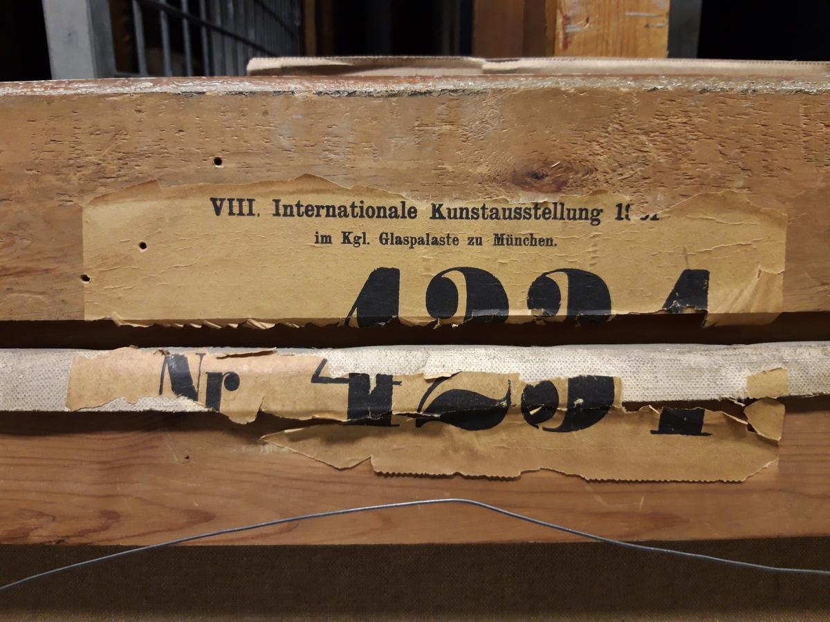 """Oljemålning på duk, """"Karoliner till häst"""" av Gustaf Ankarcrona. Målad 1901. Vinterdag i en dalaby, där karolinskt kavalleri rider in. En gubbe i röd luva har gått utomhus för att ge anvisningar. Två av ryttarna ses framifrån i tavlans förgrund.  Bronsfärgad skulpterad ram."""