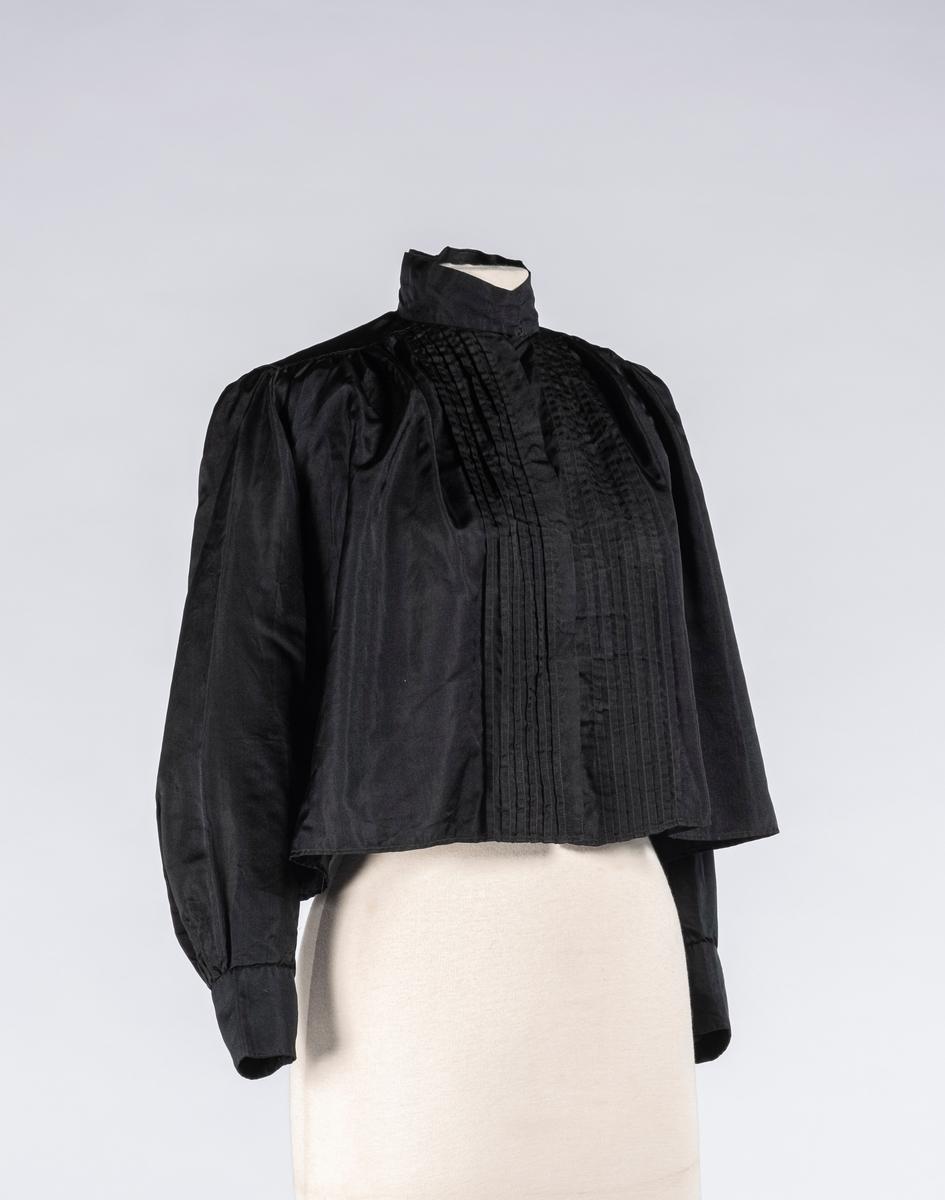 Svart kjoleliv av silke. Den har puffermer og høy hals. Det er sydd folder/brett foran ved åpningen. Kjolelivet, halsen og mansjettene lukkes med trykknapper. På baksiden er det påsydd snor trolig for snøring. Ved snoren er den en metallhekte.