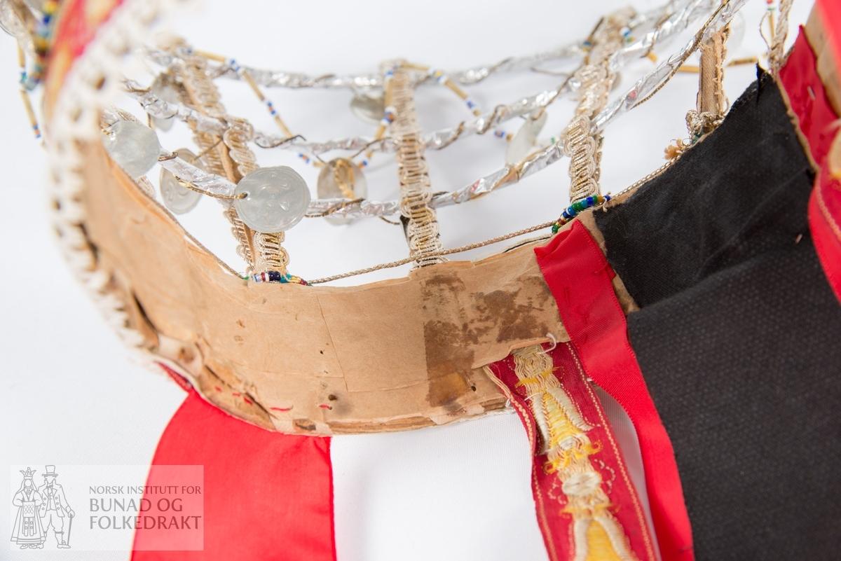 """Perlekrone. """"Jonsok-krune."""" Trosk av papp foret med papir og trukket med sølvfarget sjokoladepapir og silkebånd. Grind av vertikale korsettspiler (stofftrukket) med metallblonde og tre horisontale ringer av metallstreng med sjokoladepapir viklet rundt. Grinda er pyntet med tredde perlesnorer, metalltråd og runde «hansamerker» i tynn metallblikk. Merkene kommer fra korkene på flasker fra Hansa. Når krona er i bevegelse, høres en ringlende lyd fra merkene. Nakkebånd, noen er fornyet: 2 røde bånd i blandingskvalitet med flotterende blomstermønster, 2 røde nylonbånd og et svart blomstret silkebånd forsterket med limstoff. Brede, røde knyteband av nylon ved ørene. Trosken er kantet nede med bomullsblonde. Noen bånd skiftet ut.  Håndsydd, håndlaget, limt."""