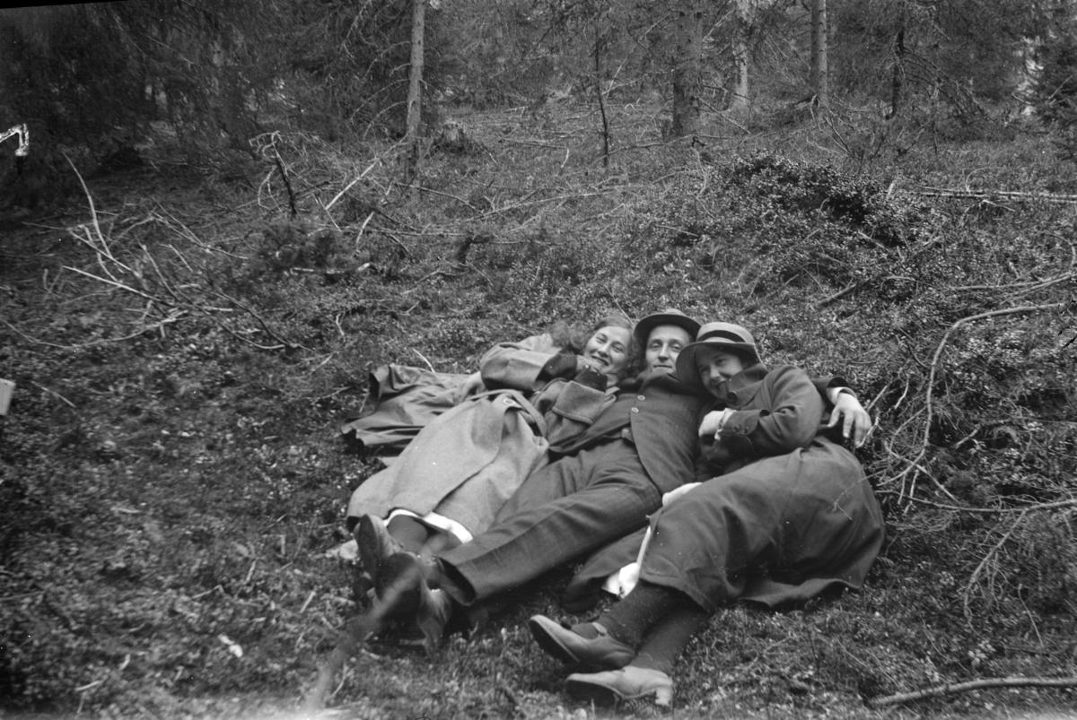 Muligens fotografen som ligger i gresset med en dame på hver side.