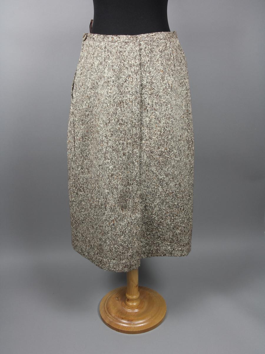 Kjol till dräkt i två delar. Av brun och gråmellerad tuskaftsvävd ull. Dekorativt veck fram och bak. Figurnära modell. Stängs med metalldragkedja och knapp i sidan. Kjolen är inte fodrad.