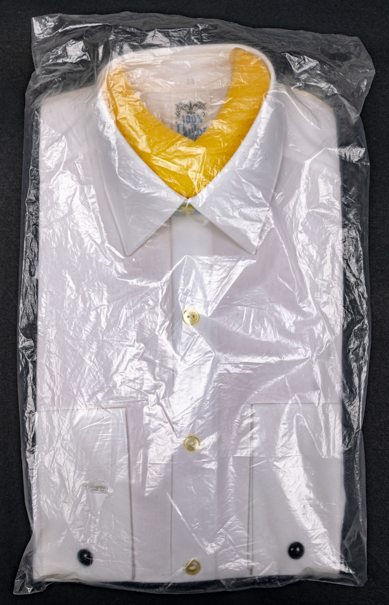 Vit nylonskjorta i originalförpackning. Skumgummibit innanför halslinningen. Vita knappar och svarta manschettknappar.