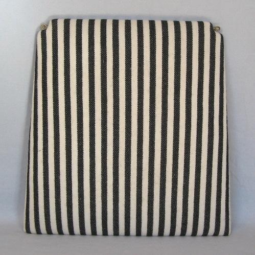 Randigt möbelöverdrag, möbeltyg monterat på stolsdyna. Ett möbeltyg vävt i korskypert med inslagseffekt på rätsidan. Varpen är av tunt blekt tvåtrådigt bomullsgarn. Inslaget är entrådigt ullgarn vävt med två trådar tillsammans i centimeterbreda ränder i svart och natrvitt.Möbeltyget är monterat med häftklammer på en stolsdyna av skivmaterial, plywood, med stoppning. Dynan är lite smalare i bakkant och där är hörnen urtagna. Två öglor i gul metall är iskruvade för upphängning. Möbeltyget är formgivet av Ann-Mari Nilsson och tillverkat av Länshemslöjden Skaraborg. Se även inv.nr. 132-134 Vävprov och Möbelklädsel i olika färgställningar samt inv.nr. 136-141 Handduk och Vävprov i samma randning och färgställning.